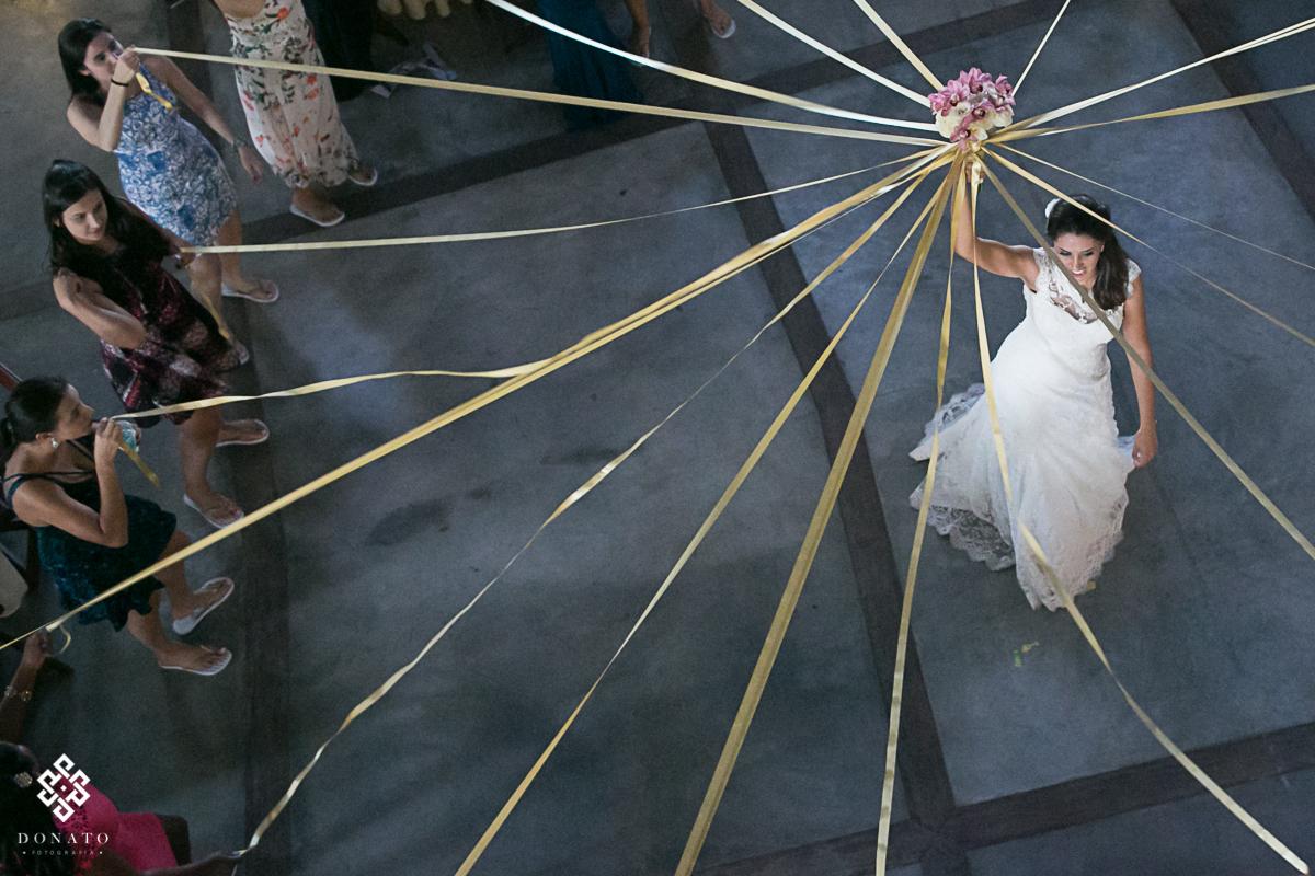 Noiva faz roda e amarra o bouquet com fitas, as convidadas pegam a fita para ver que vai ficar com o bouquet.