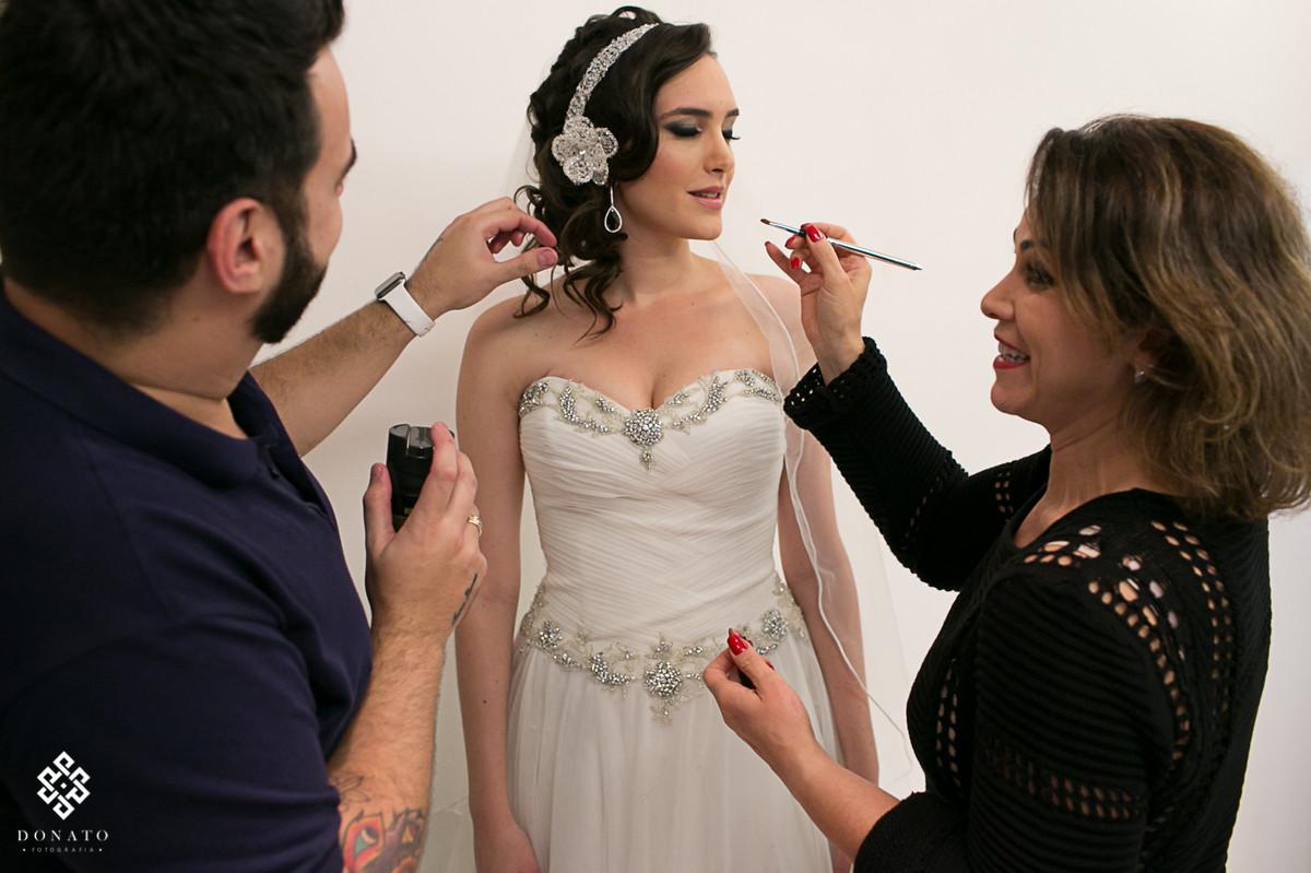 maquiadora retoca a maquiagem da noiva.