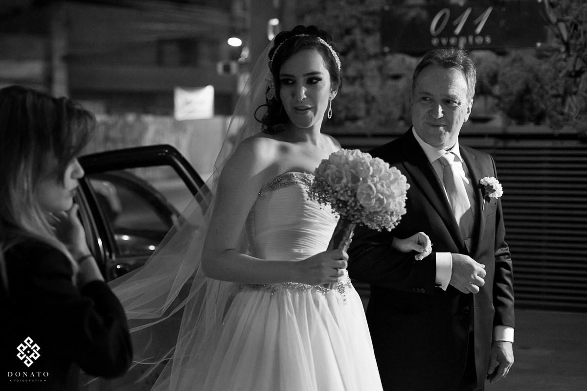 Noiva saindo do carro com seu pai, ao fundo da pra ver o logo do buffet 011 eventos.