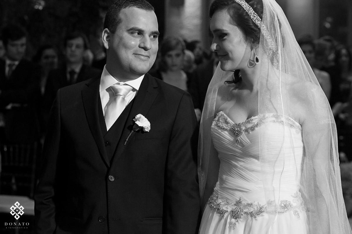 noivos se olham no altar e trocam sorrisos, a foto esta em branco e preto, dando assim um ar mais romántico a cena.