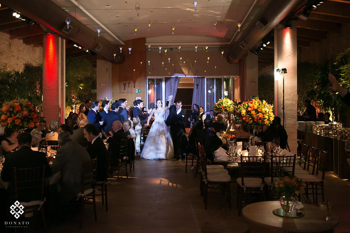 noivos entram na festa, foto muito alegre, a noiva levanta o braço comemorando, e todos os convidados comemoram juntos.