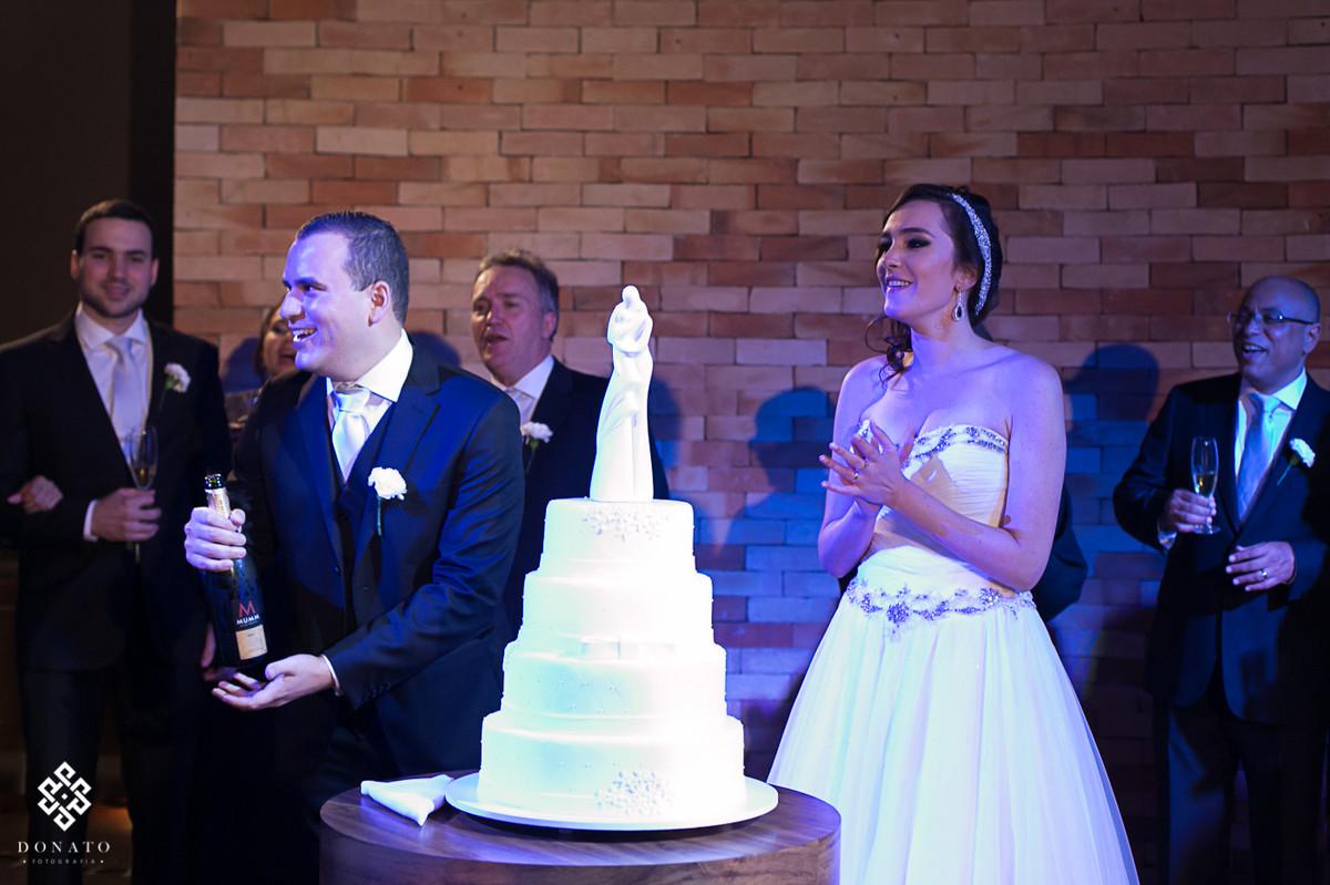 noivo estoura a champanhe, a noiva sorri e comemora junto o momento único.