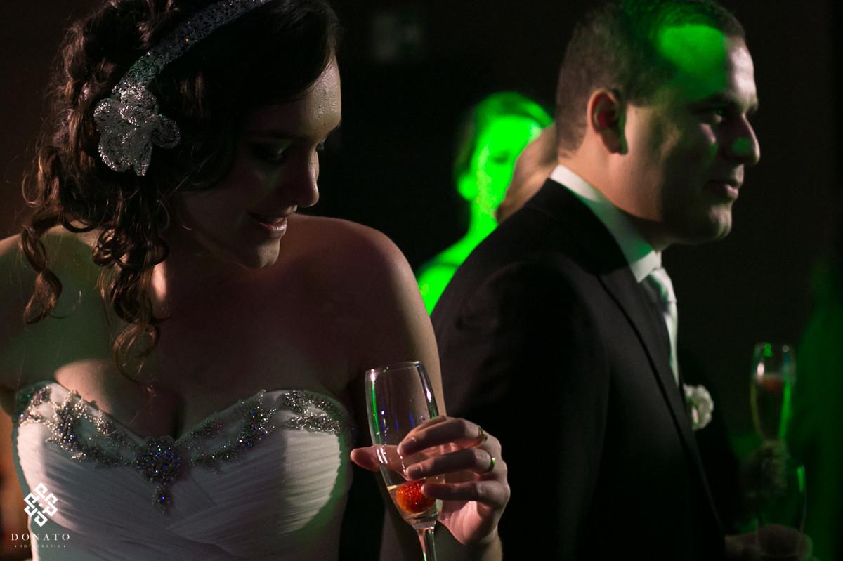noiva dança com taça na mão, com uma luz de recorte incrivel, deixando tudo ainda mais bonito.