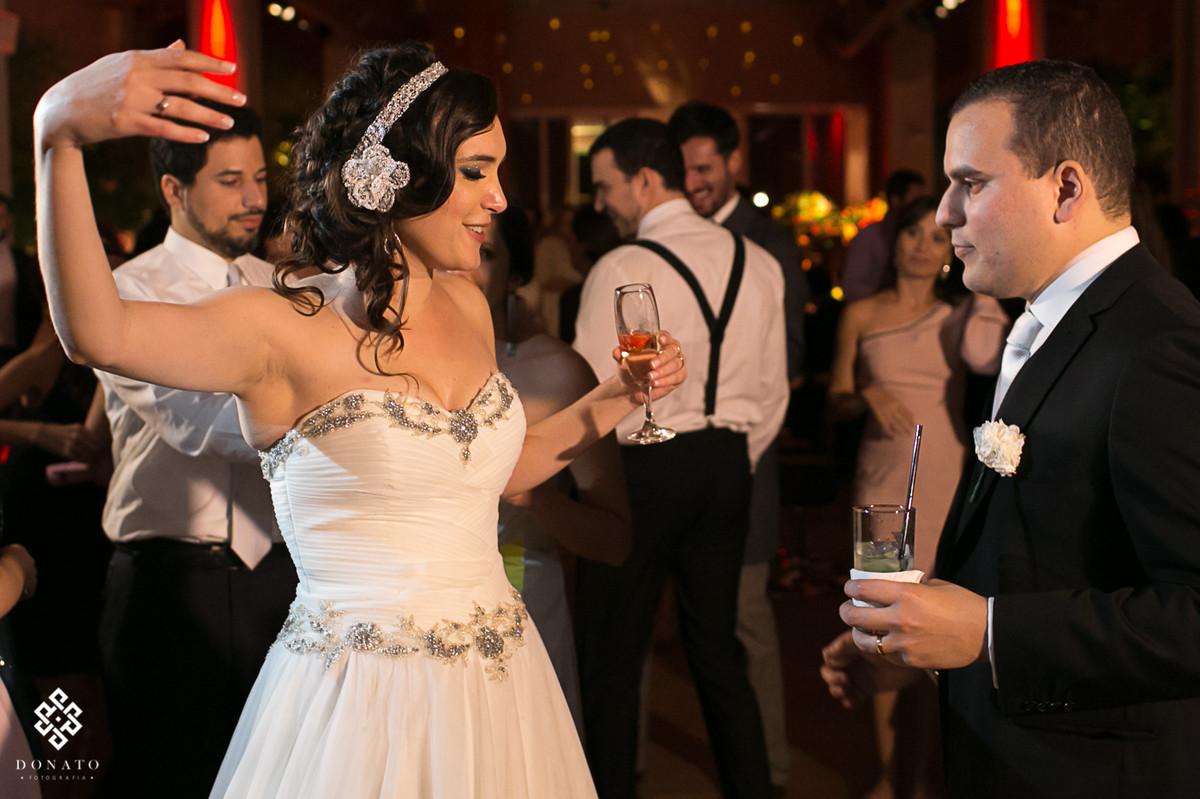Noiva dança no salo do villa bisutti, com uma taça na mão.