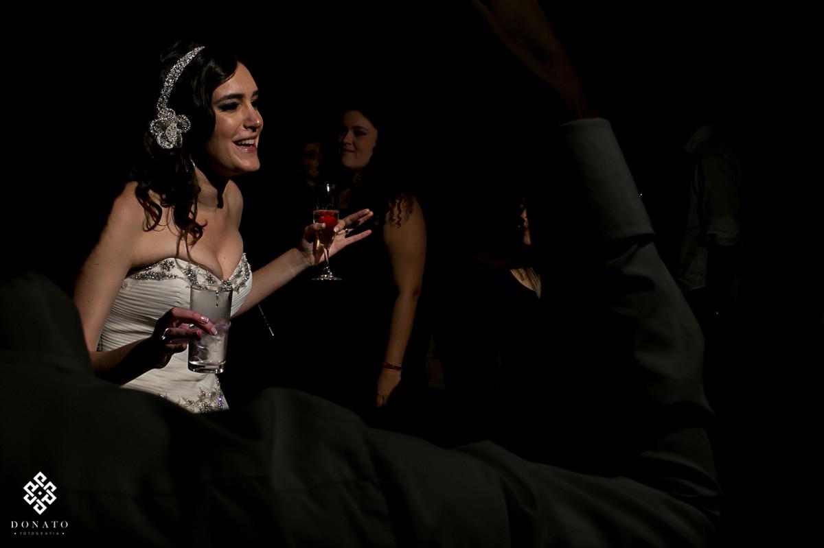 noiva detona na pista de dança, com uma taça de vinho branco na mão, se diverte muito.