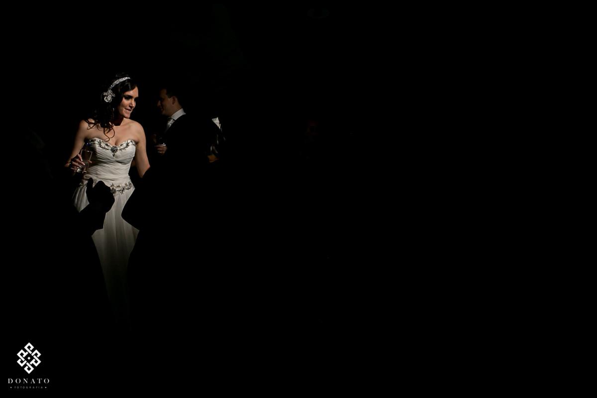 noiva em detalhe se divertindo no meio da pista, a luz utilizada deixa a noiva em evidencia entre uma grande parte escura.