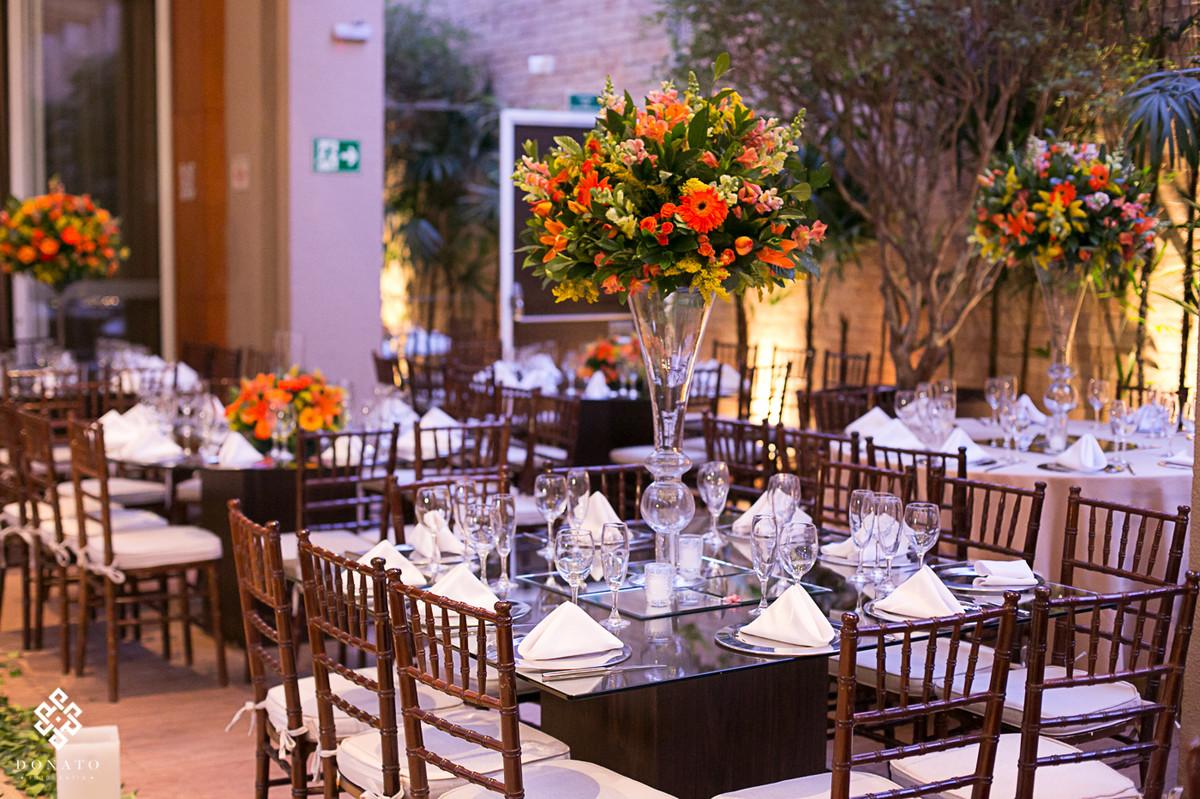 Visao geral do salao de festas do villa bisutti 011, com arranjo alto com flores amarelas e laranja.