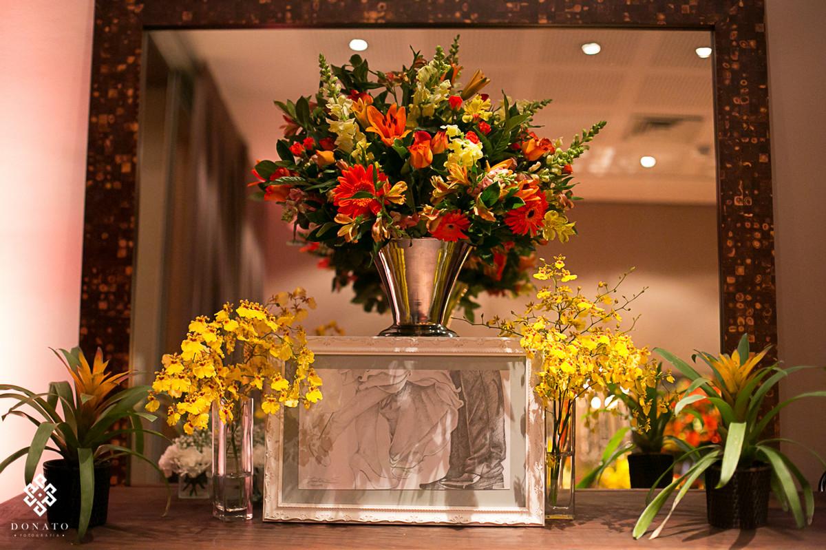 Detalhe da decoração, arranjo com flores laranja e amarelas, com um lindo quadro feito pela própria noiva em lápis.