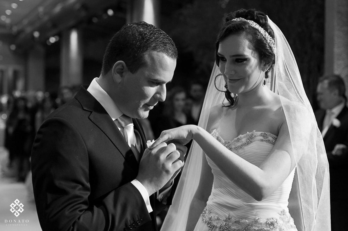 noivo beija a mão da noiva, o lindo sorriso da noiva mostra o quanto o casal se ama.