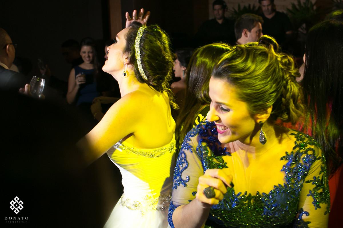 noiva e madrinhas se divertem, estao dançando com uma luz amarela muito legal.