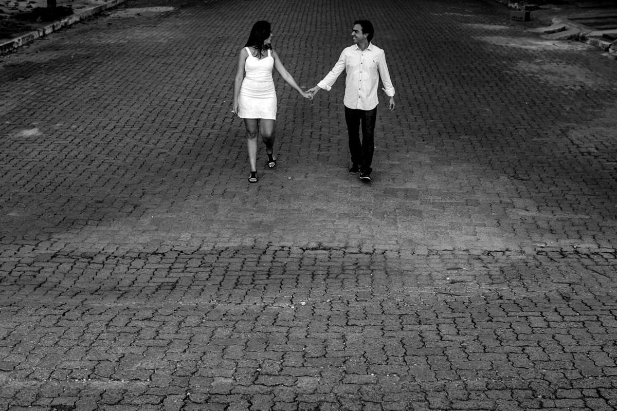 Casal passeia de mãos dadas, sobre rua de pedras, aqui a foto foi feita de cima onde pode limpar a cena como um todo, muito agradável de se ver a foto.