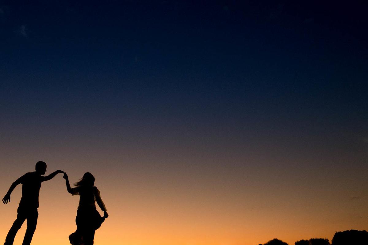 Contra luz perfeito, com casal dançando, com um por do sol alaranjado na parte de baixo e azulado na parte de cima, foto muito linda.