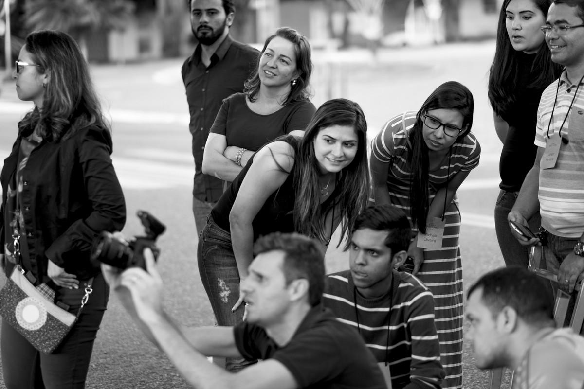 Leandro clica casal, mostrando a pratica aos alunos que ao fundo olham como fotografar em um angulo diferente.
