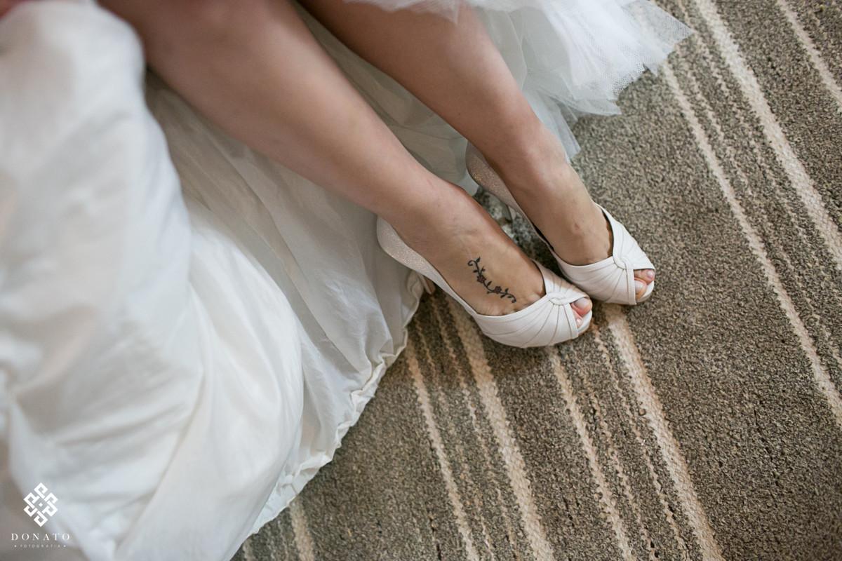 Detalhe do sabato da noiva e sua linda tatuagem com pequenas flores delicadas.