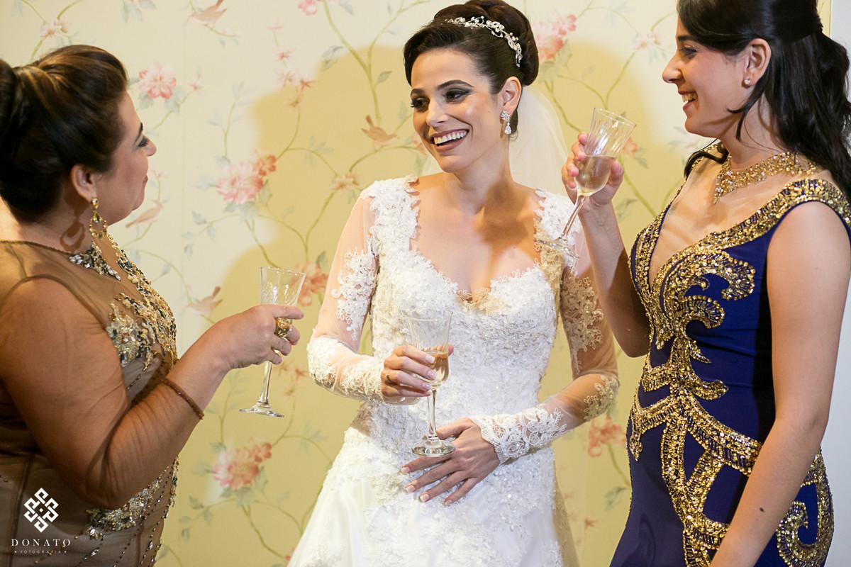 noiva já pronta brinda com irmã e mãe, tudo muito descontraído e alegre, com uma luz suave. Noiva usa vestido de renda feito por Pablo Stellai.