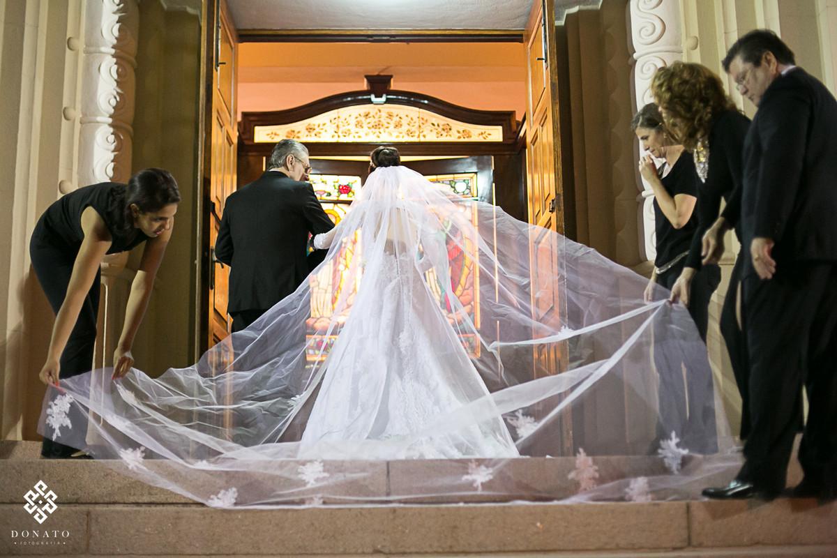 Noiva na porta da igreja, amigas arrumam o véu antes da entrada na igreja.