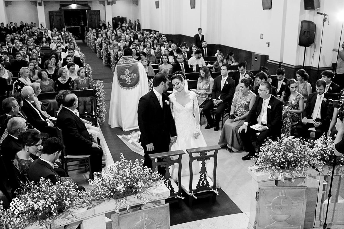 Visão geral da igreja, com noivos a frente e todos os convidados.