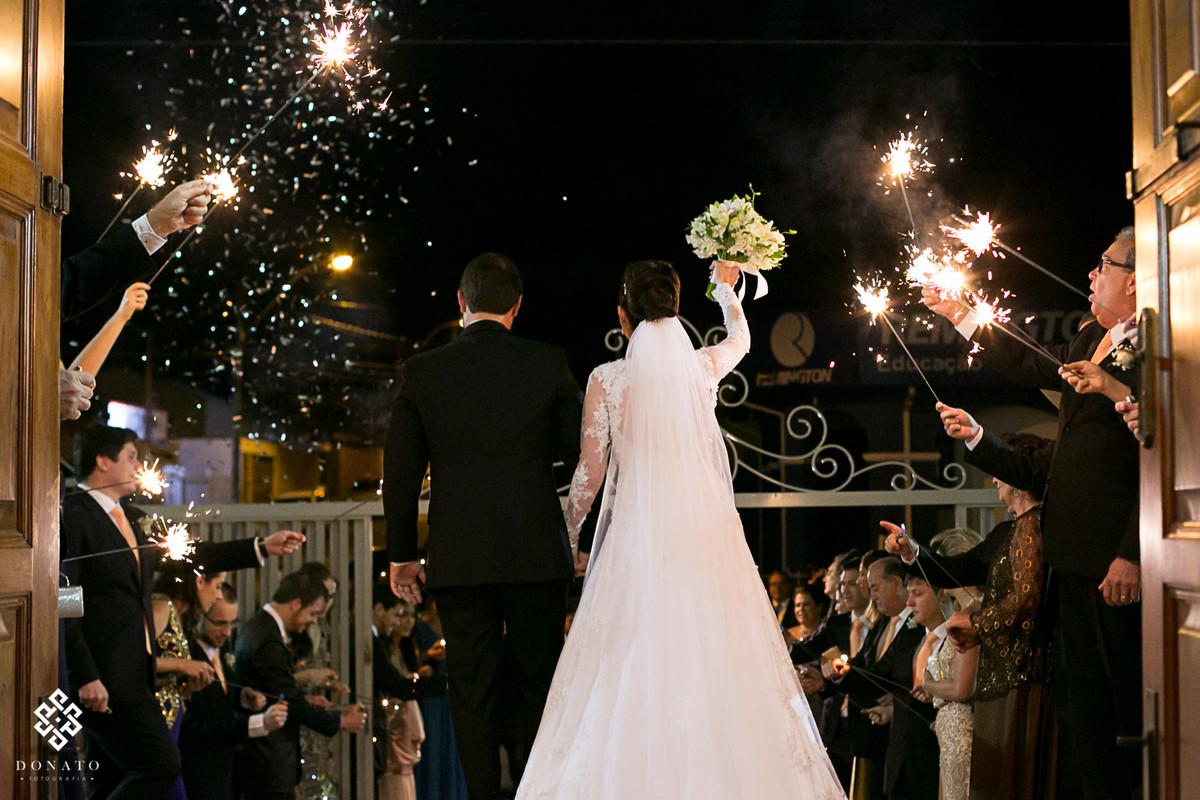 Saida emocionante dos noivos na igreja, padrinhos acendem bastoes com fogo iluminando e fazendo deste momento algo ainda mais unico.