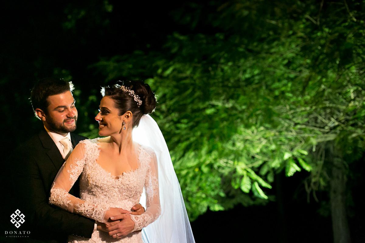Foto feita de baixo de uma arvore linda, que fica no jardim do buffet Flamboyant, a arvore esta toda verde ao fundo e os noivos com um tom quente que remete a paixão.