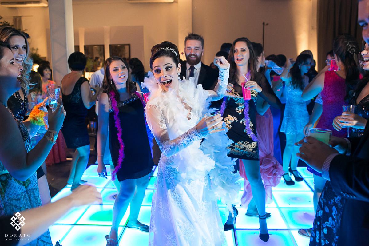 Noiva dançando com amigos, sobre uma pista de led azul, momento perfeito.