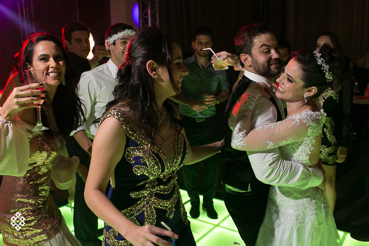 Noiva abraça o noivo e dança, com sua irmã ao lado se divertindo pra valer.