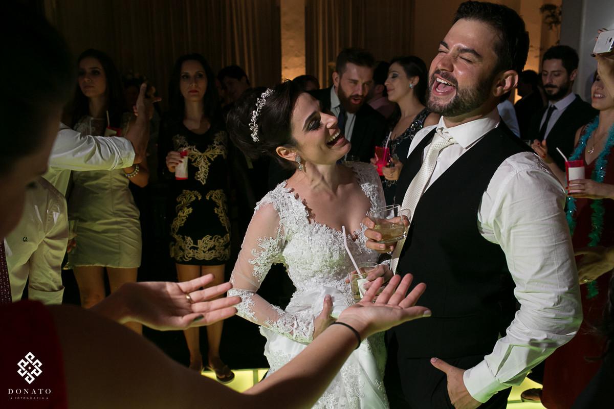 Noivo solta um grito na pista de dança, a noiva ao lado canta alguma musica muito divertida.