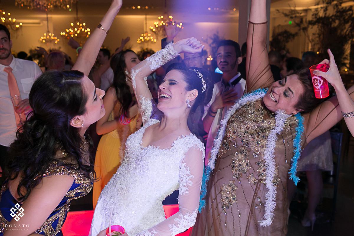 Noiva, mãe e irmã, dançam pra valer, fazendo um movimento unico e sincrionizado com o corpo para trás, muito legal ver este sincronismo na família, mesmo quando estão se divertindo.