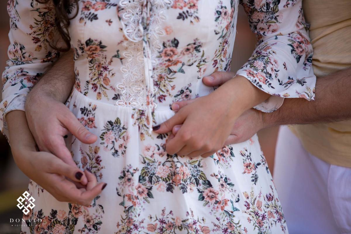 detalhes das maos, um close do carinho, a noiva usa um vestido claro e florido.