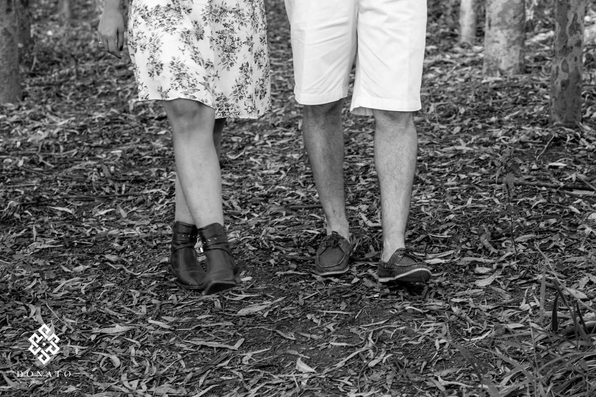Detalhes dos pés do casal, a foto esta em preto e branco, sobre folhas de eucaliptos.
