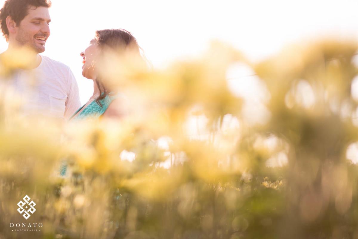 Casal se diverte entre margaridas amarelas, as flores estão borradas.