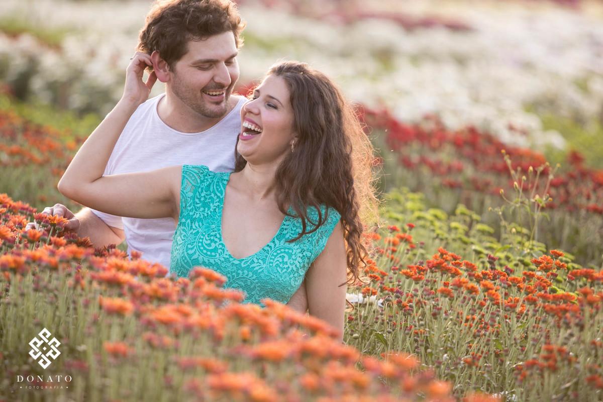 Um sorriso muito bonito do casal, a foto foi feita em diagonal, formando linhas laterais de flores laranja, verdes, vermelhas e brancas ao fundo.