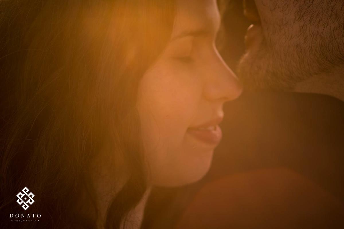 Noivos se encostam com os rostos, enquanto um luz dourada entra na imagem.
