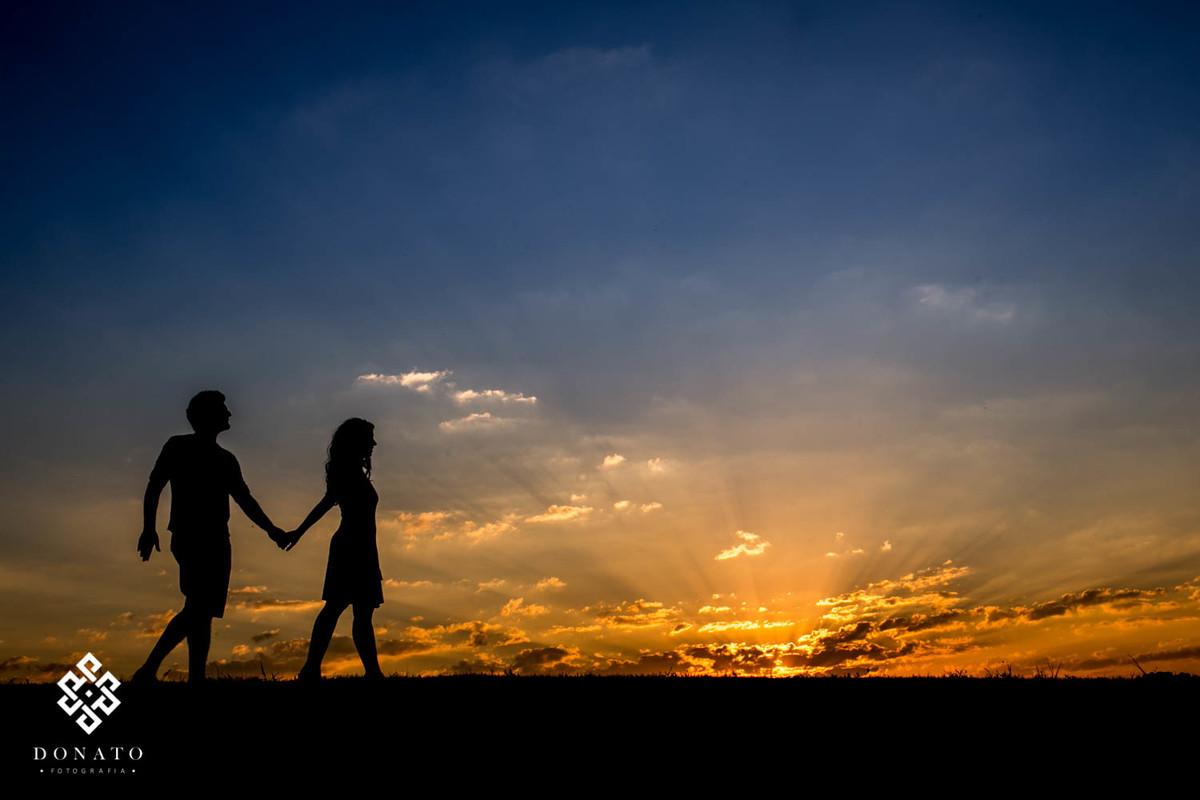 noivos caminham de maos dadas em frente a um lindo por do sol, a imagem tem um ceu azul maravilhoso e a pate de baixo toda dourada do sol.