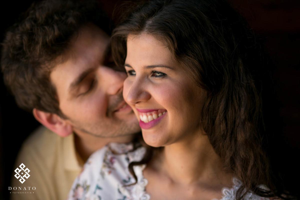 A noiva sorri com seu lindos olhos verdes, enquanto o noivo da um cheiro no pescoço, a luz é suave e a imagem encantadora.