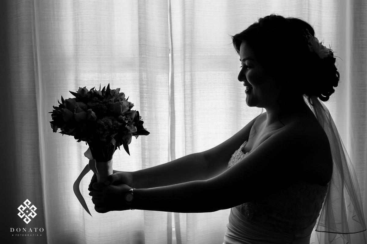 Noiva segura um bouquet de flores, a foto esta em branco e preto, toda em silhueta.