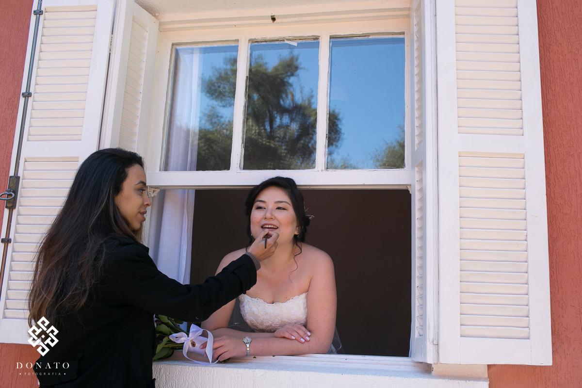 maquiadora retoca a maquiagem da noiva na janela do quarto.