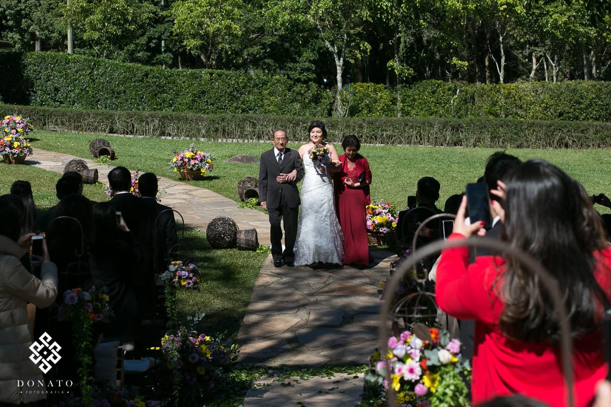 Entrada da noiva com seu pai e mae, uma entrada diferente, ao fundo as arvores que encanto o espaço natureza.