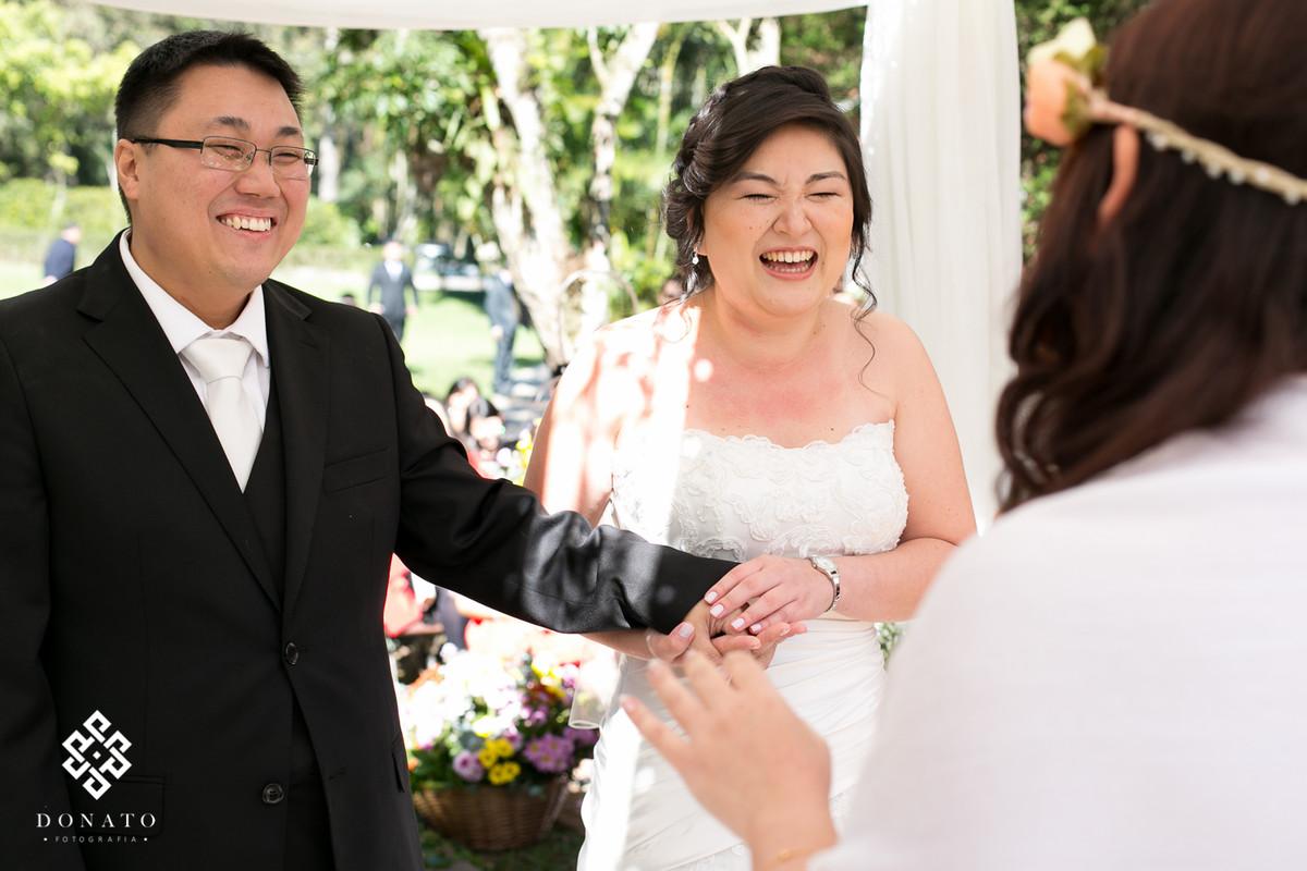 Noivos dão risadas durante a cerimonia realizada no espaço natureza.