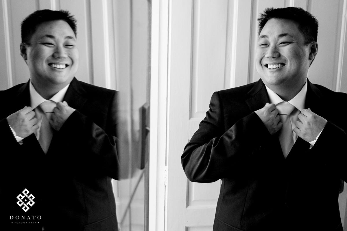 Noivo arruma a gravata em frente o espelho do quarto dele.