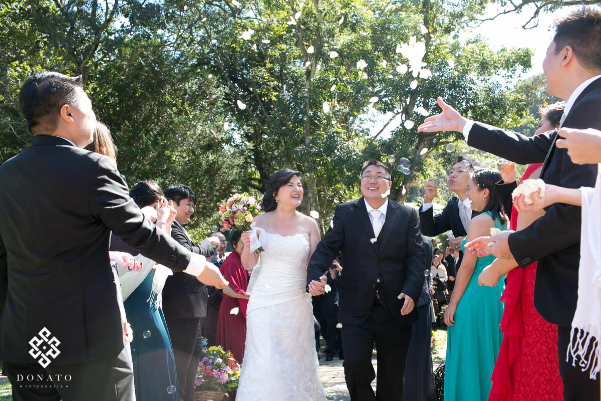 saida dos noivos da cerimonia, os padrinhos jogam pétalas de flores, os noivos sorriem, o casamento foi durante o dia, o que deixou a imagem ainda mais bonita.