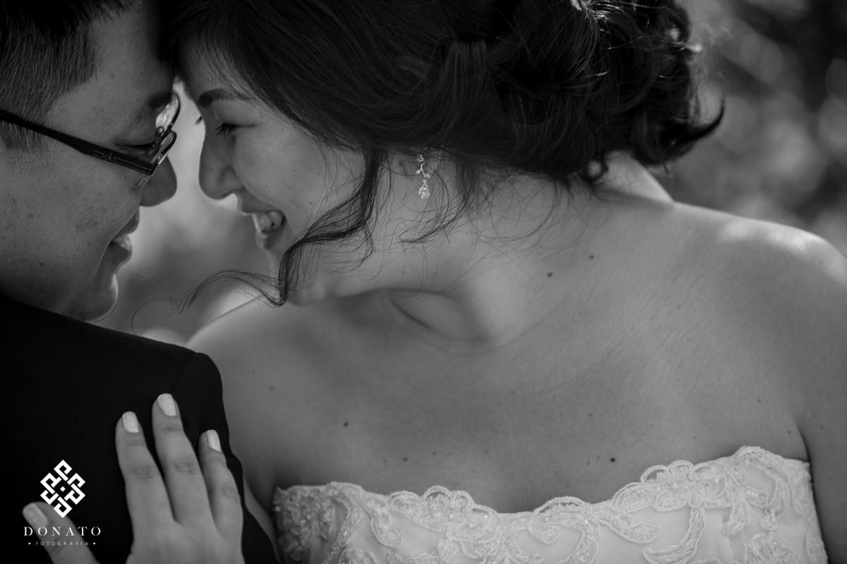 noiva namora com o noivo, a imagem é linda e romântica. O local ajuda por ser durante o dia e em meio a natureza.
