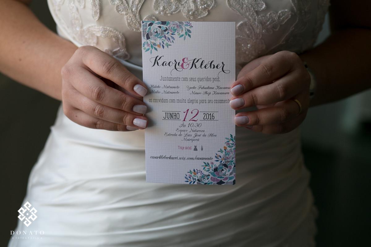 Noiva segura na mao o convite do casamento, a foto é do detalhe da mao com o convite.
