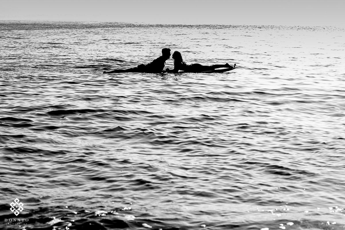 noivos se beijam na prancha de surf, dentro do mar, em silhueta e com uma imagem forte em preto e branco.