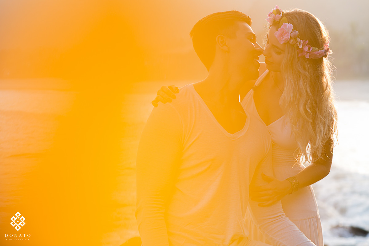 Um beijo dos noivos na praia do guaruja, uma imagem amarelada da um ar de romantismo.