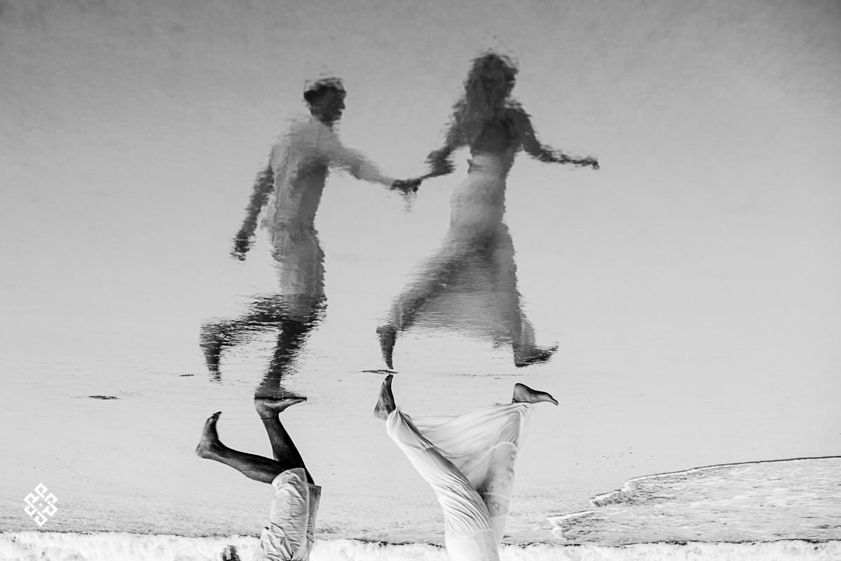 noivos correm de mãos dadas na agua do mar, a imagem é refletida na areia da praia, a foto é incrível.