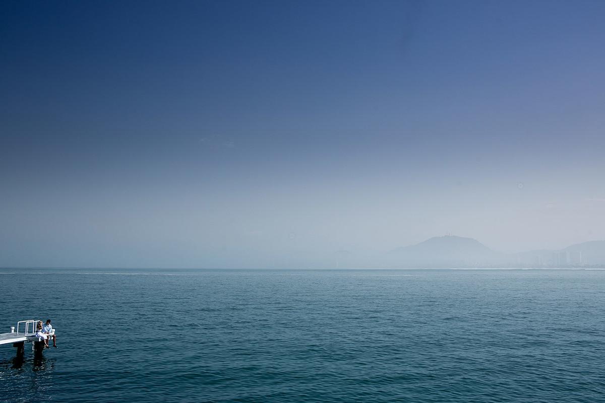 noivos em detalhe, sentados no pear, com um mar azul e o cel ao fundo.