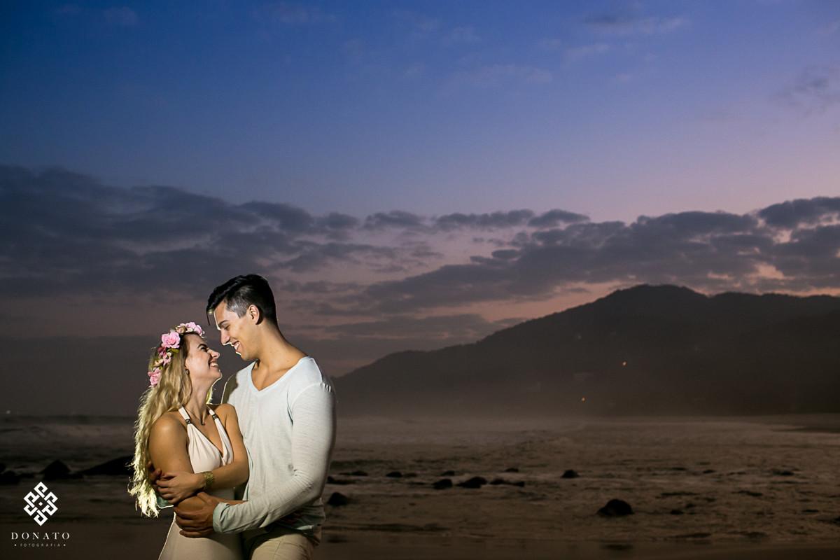 foto do pre wedding, com noivos abraçados na praia e o por do sol ao fundo.