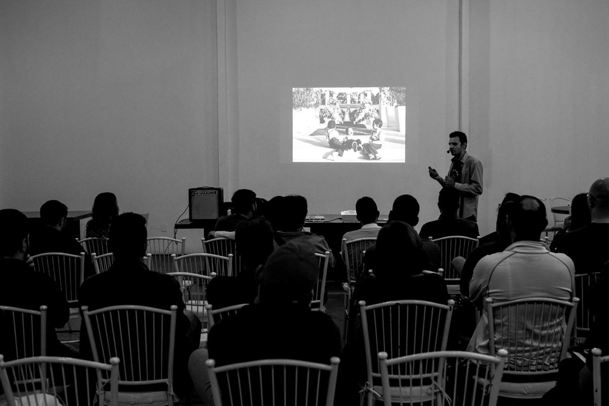 Donato palestra na frente de mais de 100 alunos, na tela ele mostra uma parte do seu curso de fotografia.