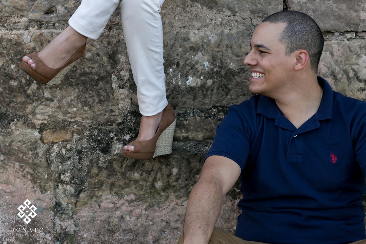 foto dos pes da noiva, e o noivo olhando para ele dando uma risada muito divertida.