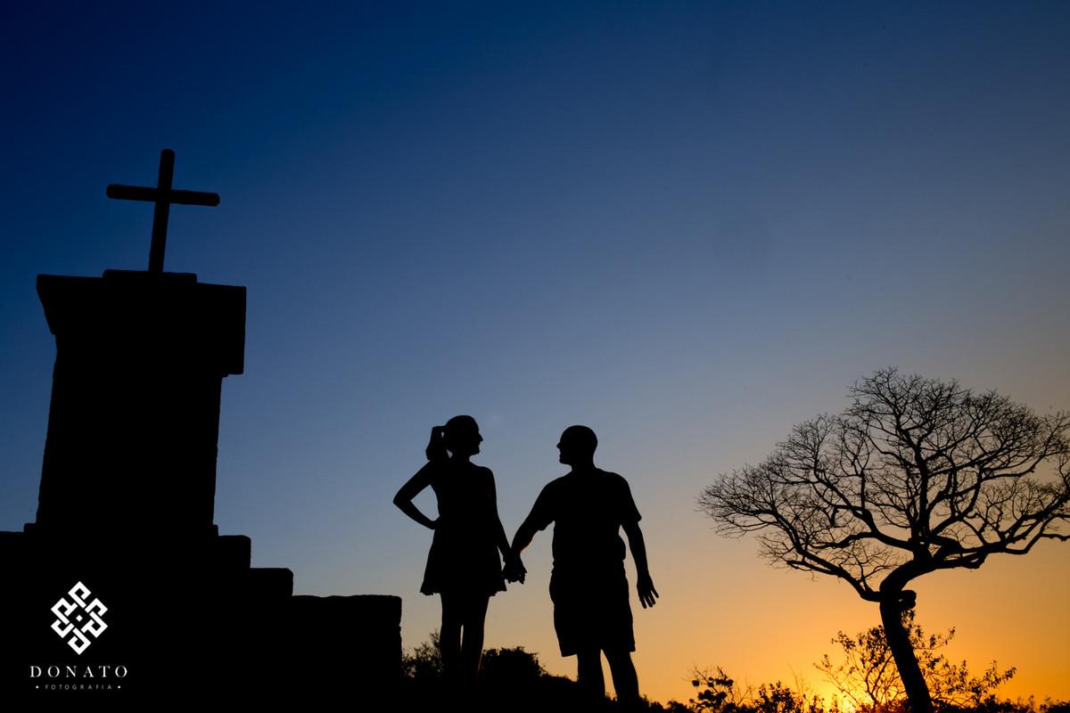 Foto em silhueta dos noivos entre a cruz e uma arvore seca, foto linda.